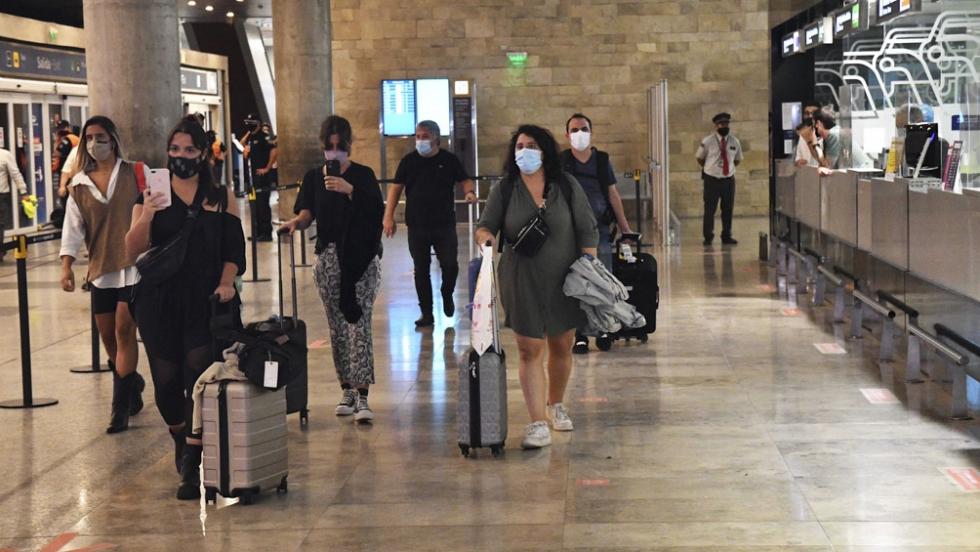 aeropuerto pandemia viajeros con barbijos.jpg